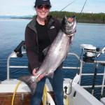 sunset charters guest holding up a good sized chinook salmon