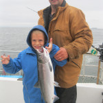 Child holding up fish - sunset Charters