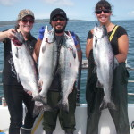 Guide and two guests holding up 4 big salmon - Sunset Charters